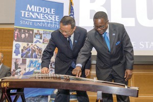 MTSU President Sidney A. McPhee, right, and Hangzhou Normal University President Du Wei pluck a few strings on a guzheng, a Chinese musical instrument, that was donated by Hangzhou Normal as the first instrument for MTSU's new Chinese Music and Cultural Center. MTSU and Chinese dignitaries announced the new center Tuesday at the MTSU Student Union. (MTSU photo by J. Intintoli)