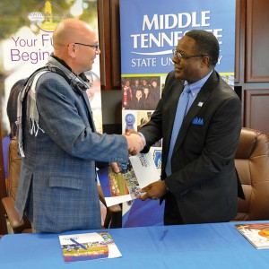 Montverde Headmaster Kasey Kesselring (left) and MTSU President Sidney A. McPhee shake hands Friday after signing a pact that will allow for dual enrollment of Montverde students, most likely through online classes by the university. (MTSU photo by Andrew Oppmann)