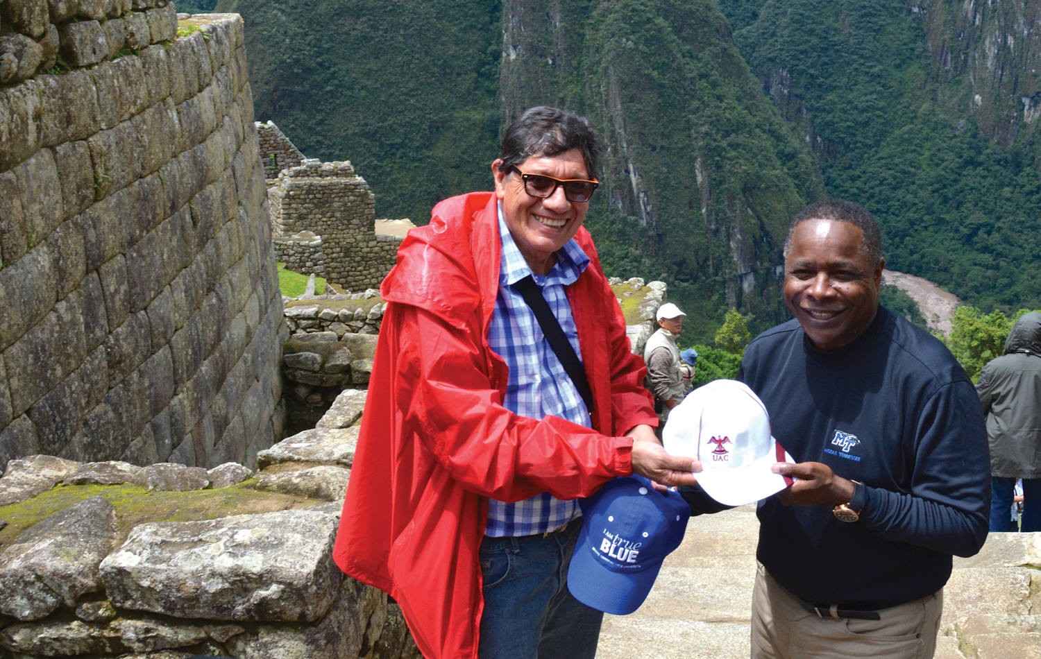 Alejandro Paul Pletickosich Picon (left), director of social responsibility and university extension at Universidad Andina Del Cusco, and MTSU President Sidney A. McPhee exchange university hats Saturday while touring the Inca Empire ruins at Machu Picchu, near Cusco, Peru. (MTSU photo by Andrew Oppmann)