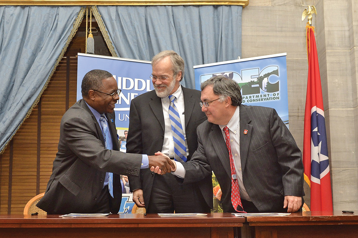 MTSU President Sidney A. McPhee, left, shakes hands with Tennessee Department of Environment and Conservation Commissioner Bob Martineau, right, after signing an agreement Thursday, April 16, at the State Capitol that will expand individual opportunities for earning MTSU course credit and certifications through TDEC's Fleming Training Center in Murfreesboro, online and at other statewide locations. Tennessee Board of Regents Chancellor John Morgan, center, also signed the agreement. (MTSU photo by Andy Heidt)