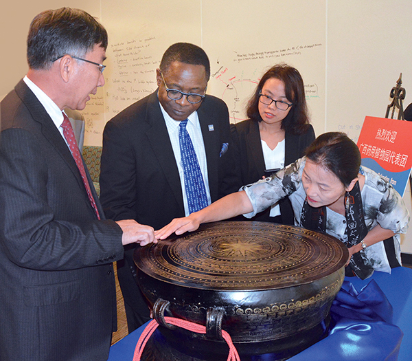 Miao Jianhua, left, director of the Guangxi Botanical Garden of Medicinal Plants in Nanning, China, presents an ancient bronze drum to MTSU President Sidney A. McPhee and Mei Han, director of MTSU's Center for Chinese Music and Culture, set to open next year. (MTSU photo by Andrew Oppmann)
