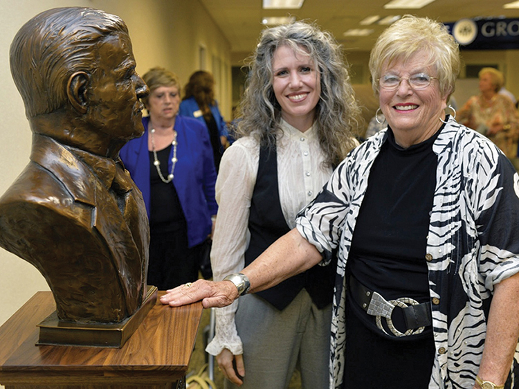 Sculptor Tracy Sugg, left, of Wartrace, Tenn., and MTSU alumna Liz Bradley of Pearland, Texas, stand next to the bronze bust of the late James M. Buchanan during a special unveiling ceremony Sept. 18 in the James E. Walker Library. Bradley, a retired former principal at Homer Pittard Campus School, is the youngest sister of Buchanan, an MTSU alumnus and university's first Nobel Prize recipient. (MTSU photo by Andy Heidt)
