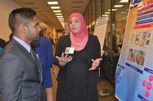 MTSU senior chemistry major Ryan Tilluck, left, of Trinidad and Tobago, listens while senior food science major Nausheen Qureshi of Murfreesboro talks about her research Feb. 24 during Posters at the Capitol in Nashville. (MTSU photo by Randy Weiler)