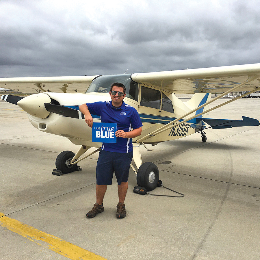 "Holding a Middle Tennessee State University ""I am true BLUE"" sign from his university after arriving at the Long Beach (California) Airport, senior Collin McDonald of Carthage, Tennessee, stands in front of ""Molly,"" the four-seat Maule MX-7-160 airplane he flew 4,300 miles across the country following the flight path of aviation pioneer Cal Rodgers in 1911. McDonald achieved this for an Honors College thesis project and to promote avaiation to young people and adults at the 75 stops along the way. (Photo by Lorrie McDonald/vinfizflight.wordpress.com)"