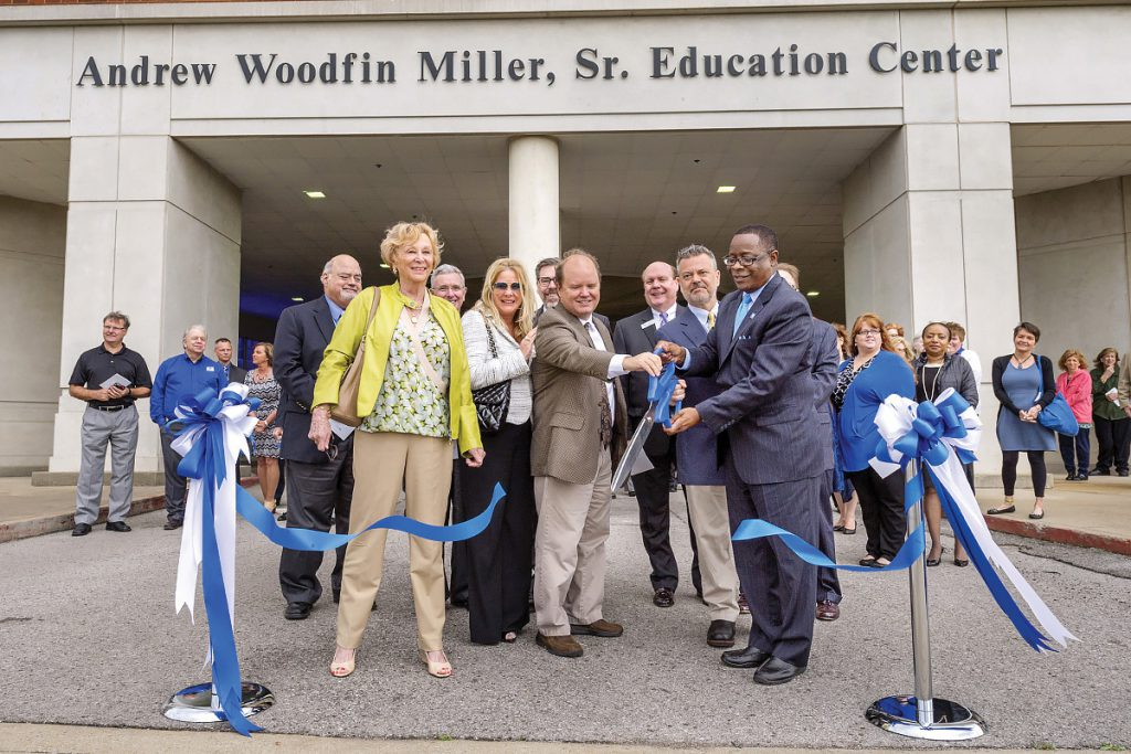 MTSU President Sidney A. McPhee, right, helps cut the ribbon Monday, March 14, before an open house for the Andrew Woodfin Miller Sr. Education Center at 503 E. Bell St. Helping McPhee are Miller Sr.'s sons, Andrew Miller Jr. and Tracy Miller. (MTSU photo by J. Intintoli)