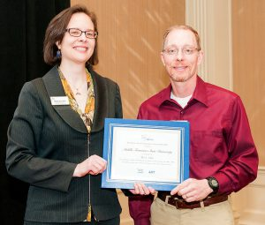 PhysTEC Director Monica Plisch, left, presents MTSU Department of Physics and Astronomy chair Ron Henderson a certificate for MTSU being a member of The 5+ Club for its contributions to producing at least five physics educators. Awards were presented March 12 in Baltimore, Maryland. (PhysTEC photo by Ken Cole)
