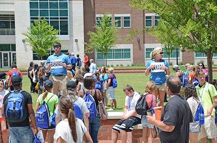 CUSTOMS Student Orientation Assistants use signs to gather new students before they head to their next destination during a 2013 orientation session. (MTSU file photo by MTSU News and Media Relations)